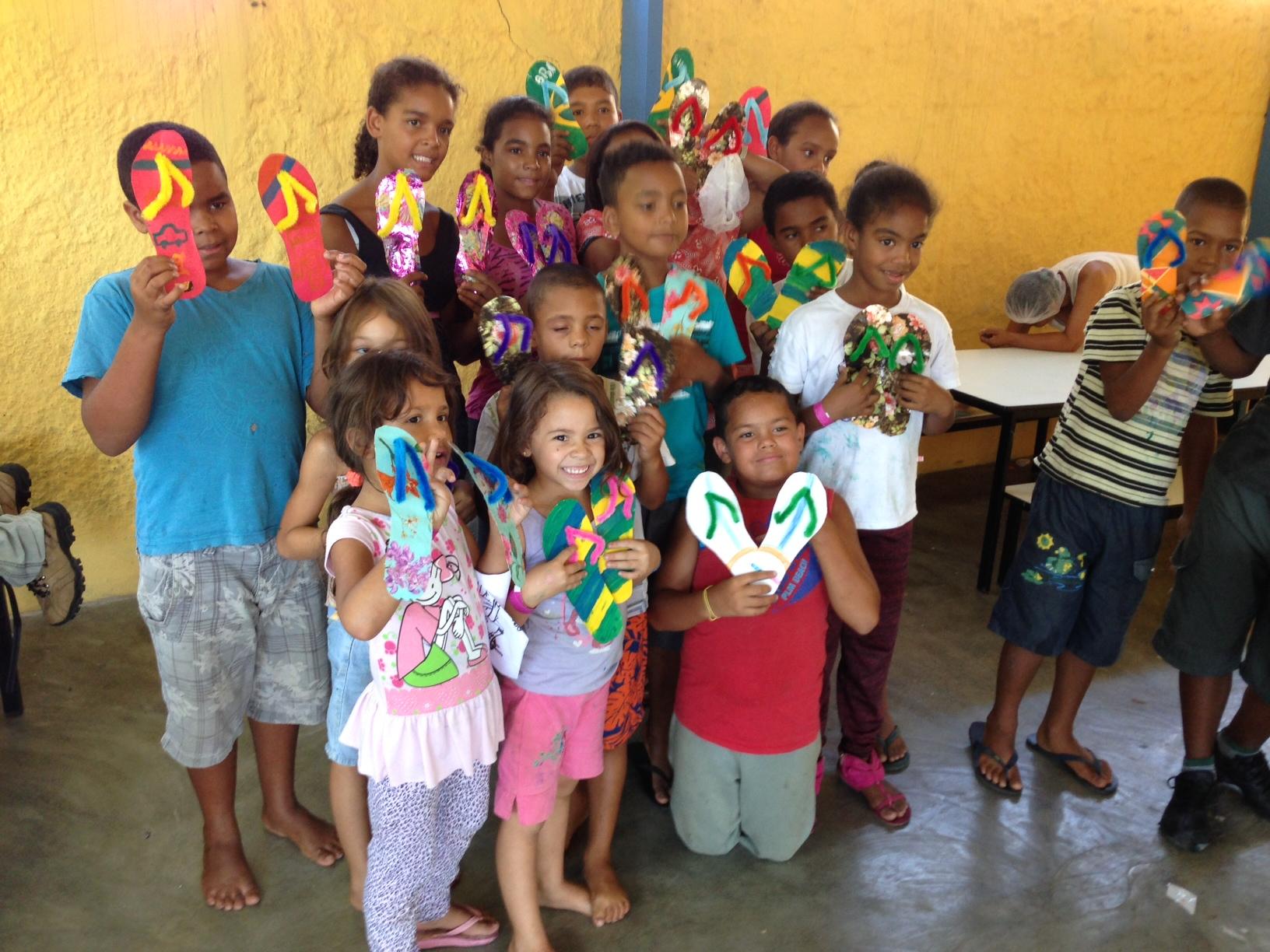 Crianças com o resultado do seu trabalho de pintura e colagem.