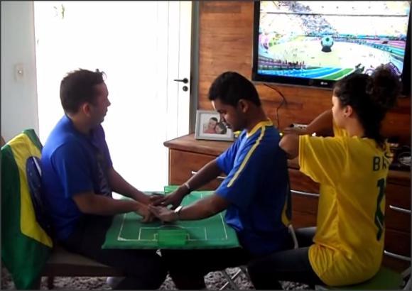 Casal ajuda amigo cegosurdo a assistir jogo. Foto: Divulgação