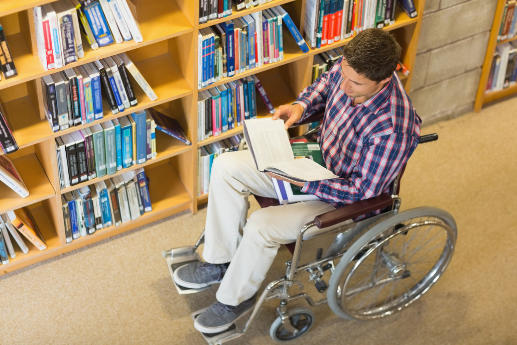 High angle view of a man in wheelchair reading a book in the lib